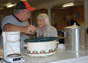 Bob Pasero, left, dishes up a steamy bowl of navy bean soup for longtime Orland resident Kay Larsen at the fourth annual Soup Bowl on Saturday.
